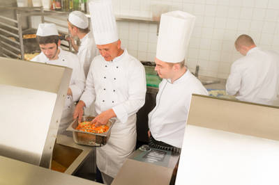 Professional chef cook with team prepare food in industrial kitchen